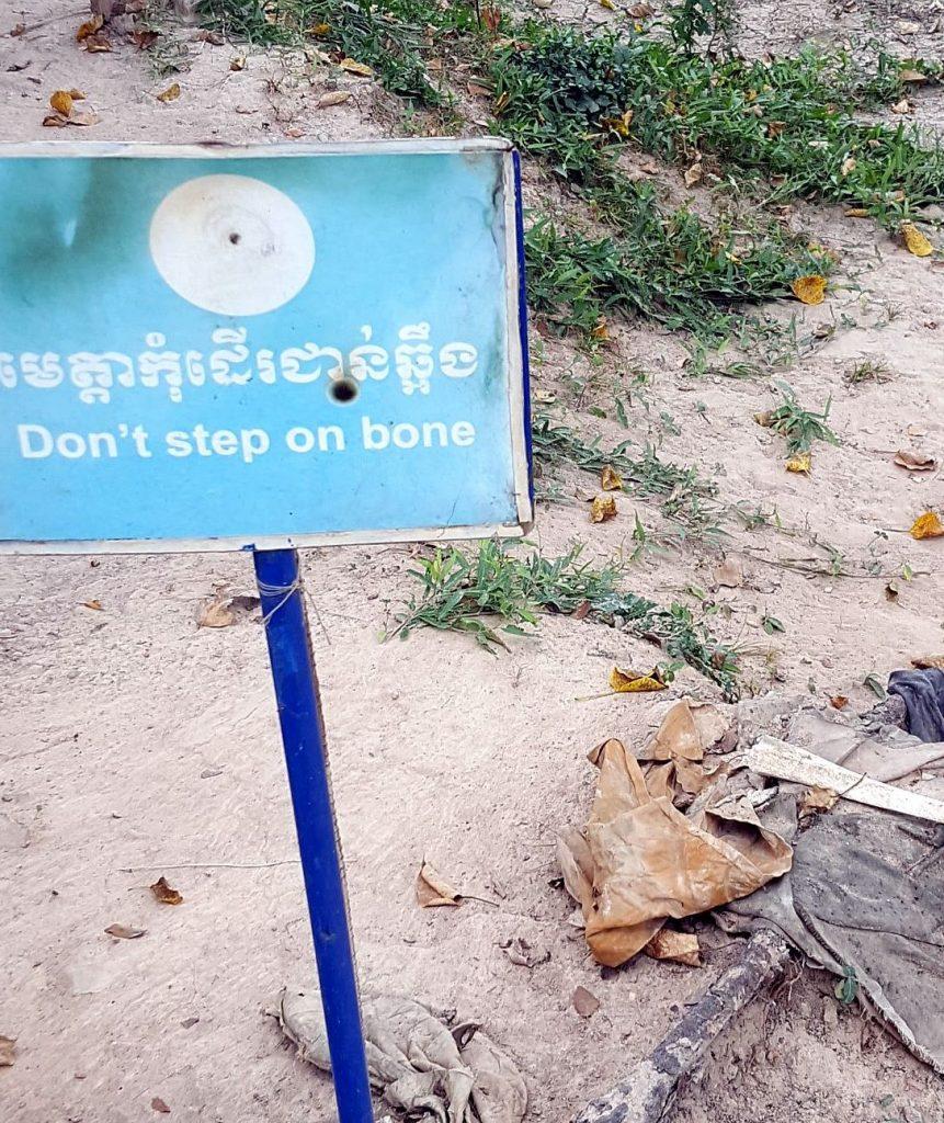 """Hinweisschild neben Menschenknochen auf den Killings Fields in Kambodscha: """"Don't step on bone - Treten Sie nicht auf Knochen"""""""