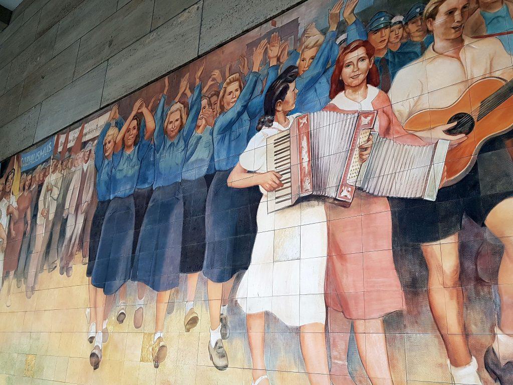 DDR-Jugendliche in FDJ-Blusen marschieren begeistert für den Sozialismus - Wandfries am Bundesfinanzministerium