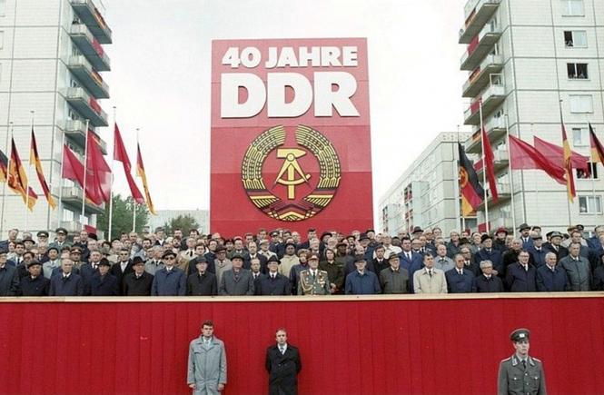 Berlin: 40. Jahrestag DDR/ Parade/ Offizieller Bildtext der DDR: Eine Ehrenparade der Nationalen Volksarmee leitete die Feierlichkeiten am 7.Oktober ein. Auf der Ehrentribüne in der Karl-Marx-Allee wurden herzlich begrüßt der Generalsekretär des ZK der SED und Vorsitzende des Staatsrates der DDR, Erich Honecker, und weitere Mitglieder der Partei- und Staatsführung der DDR sowie der Generalsekretär des ZK der KPdSU und Vorsitzende des Obersten Sowjets der UdSSR, Michail Gorbatschow (7.v.l.), und weitere Repräsentanten aus dem Ausland.