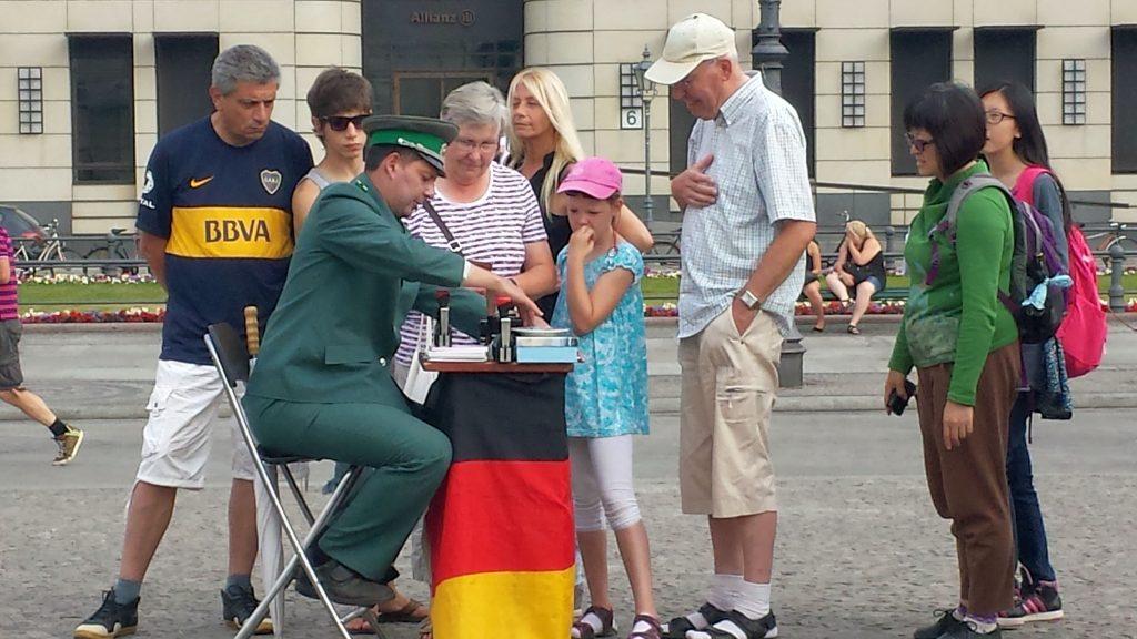 """""""Visa"""" für Touristen – verkleideter DDR-Grenzoffizier am Brandenburger Tor in Berlin"""
