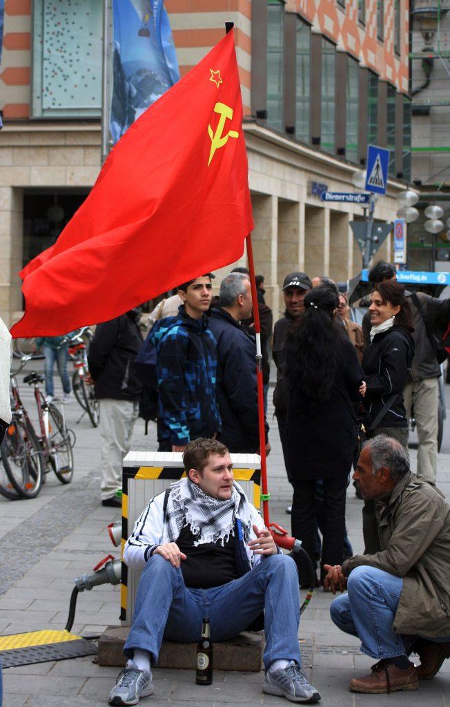 Demonstrant mit Hammer-und-Sichel-Fahne in München 2011