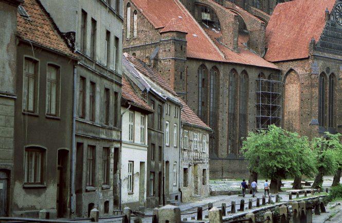 Verfallene Häuser in der Innenstadt von Wismar während der SED-Herrschaft in der DDR. Im Hintergrund die Nikolaikirche.