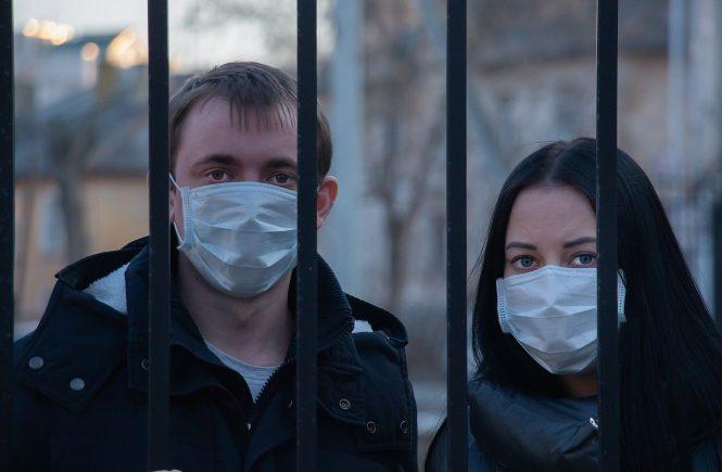 Das Foto zeigt ein junges Paar hinter Gittern während der Corona-Pandemie